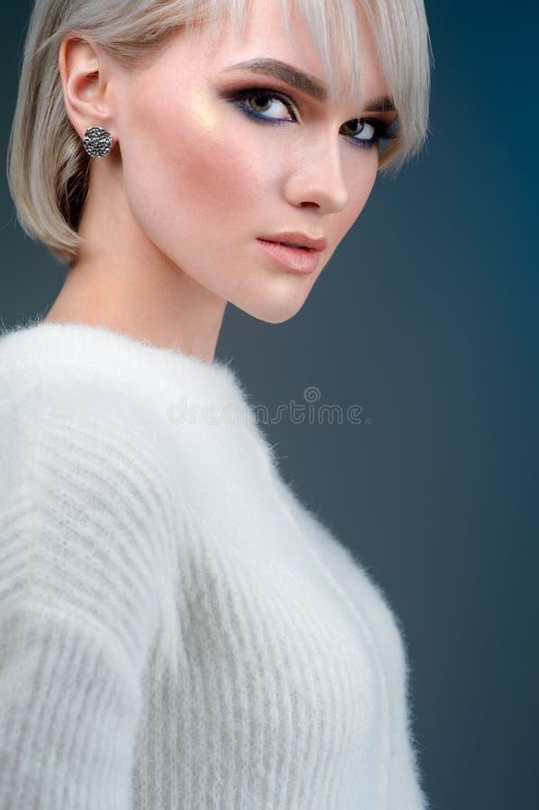 Het mooie dichte omhooggaande portret van het vrouwengezicht van een jong blonde in de studio op blauwe achtergrond stock foto's