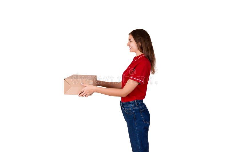 Het mooie die leveringsmeisje geeft een kartondoos aan een klant op witte achtergrond wordt geïsoleerd stock foto