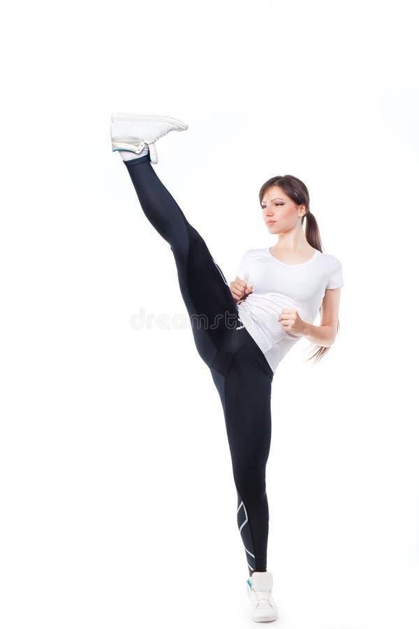 Het mooie die meisje schoppen met het been op witte achtergrond wordt geïsoleerd royalty-vrije stock foto's