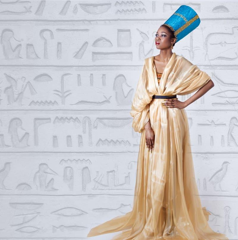 Het mooie donker-gevilde meisjeszwarte in het beeld van de Egyptische koningin met rode lippen heldere make-up toont lange spijke royalty-vrije stock foto's