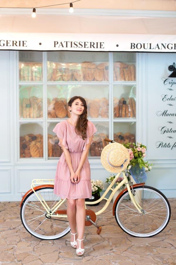 Het mooie donkerbruine meisje bevindt zich dichtbij de gele fiets met een mand Portret van een jonge dame in een kleding die een  stock foto