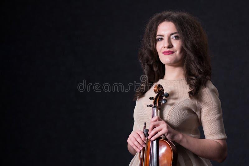 Het mooie donkerbruine meisje in een lichte beige kleding houdt een viool Concept voor muzieknieuws De ruimte van het exemplaar stock afbeeldingen