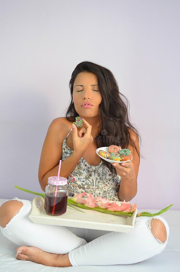 Het mooie donkerbruine meisje geniet van heerlijke donuts stock foto's