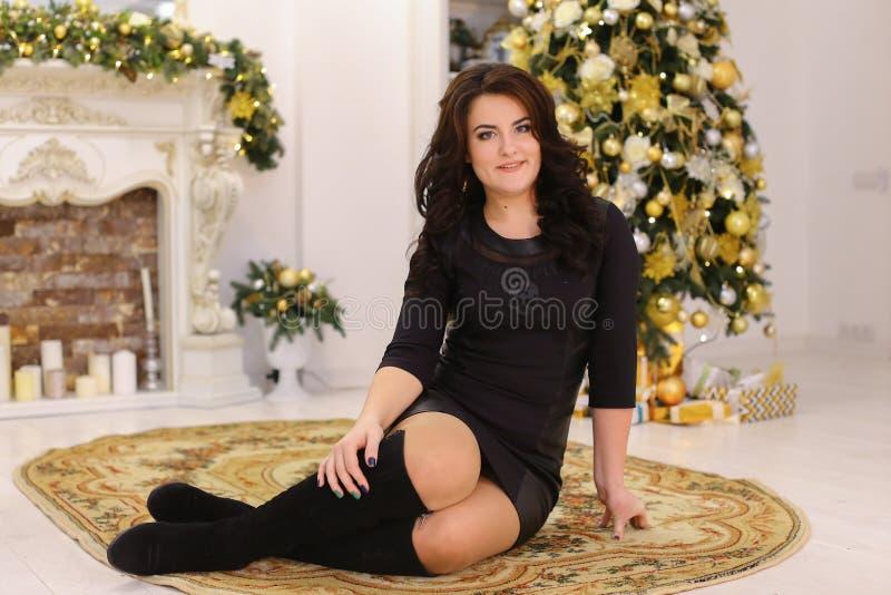 Het mooie donkerbruine meisje glimlacht en stellend terwijl het zitten op backg royalty-vrije stock afbeeldingen