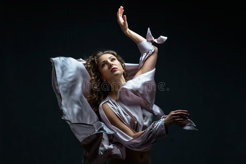 Het mooie donkerbruine meisje met krullend haar in de duisternis en licht in sexy zilveren ontzagwekkende satijn vliegende kledin royalty-vrije stock afbeelding