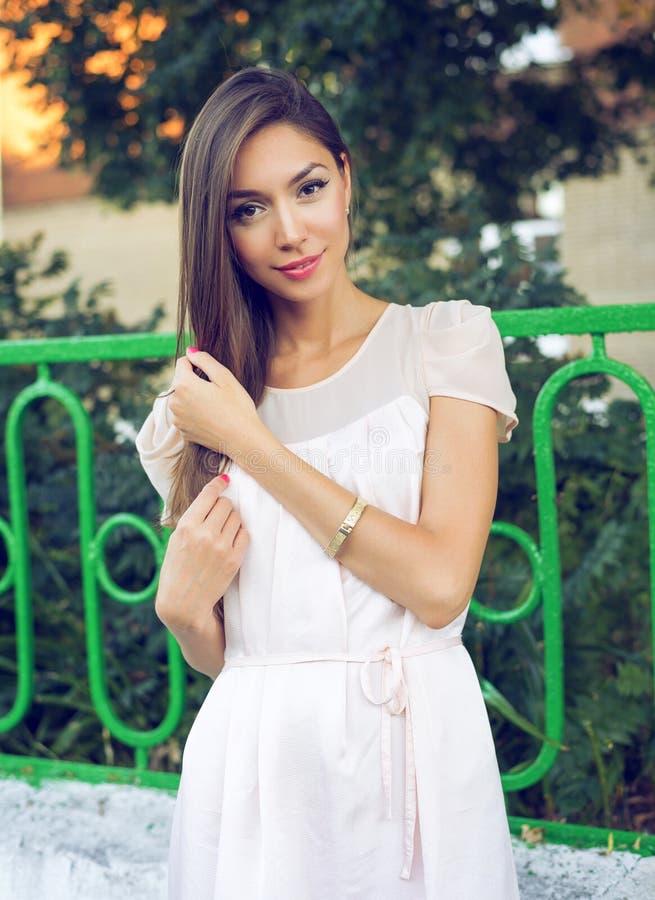 Het mooie donkerbruine meisje met lang haar in openlucht, de zomerstad, heldere lippenstift roze kleding, looide huid Gelukkige z stock fotografie