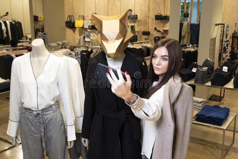 Het mooie donkerbruine meisje neemt een beeld van zich op de telefoon in een kledingsopslag Selfies naast ledenpoppen terwijl het stock foto's