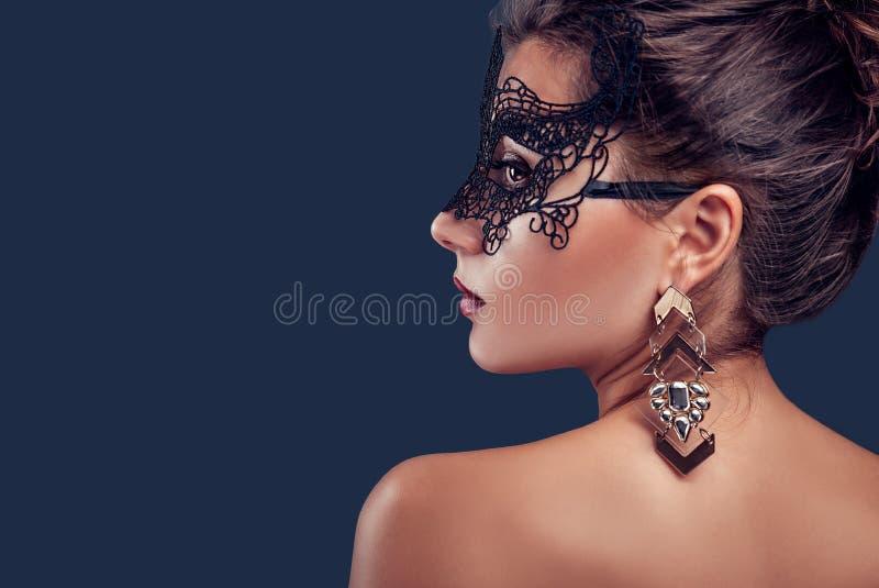 Het mooie donkerbruine model dragende masker en de juwelen van kantcarnaval Nieuwe jaarpartij stock fotografie