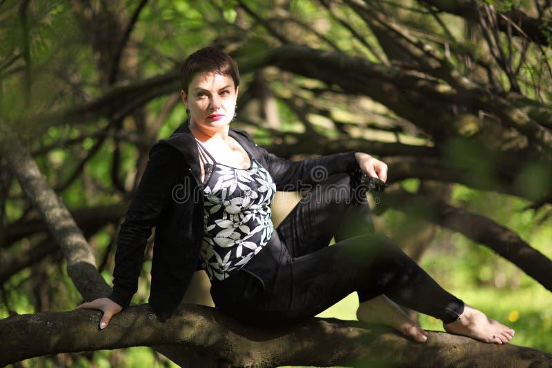 Het mooie donkerbruine stellen in het park Portret van een onbezorgde volwassen vrouw in een zwarte kleding royalty-vrije stock foto