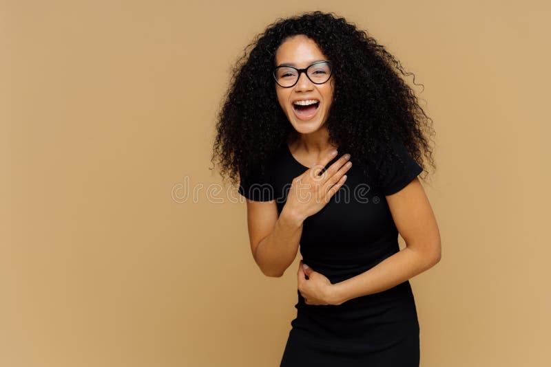 Het mooie donkere gevilde model kan niet ophouden lachend, hoort grappig verhaal, houdt hand op buik, luid lacht, gekleed in zwar stock foto