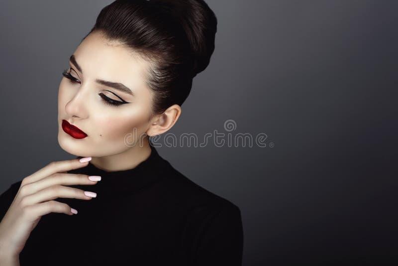 Het mooie donkere haired model met perfecte die artistiek maakt omhoog en haar terug in een hoog broodje wordt geschaafd stock foto's