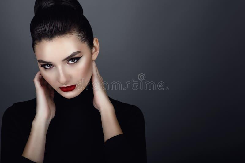 Het mooie donkere haired model met perfecte die artistiek maakt omhoog en haar terug in een hoog broodje wordt geschaafd houdend  royalty-vrije stock foto's