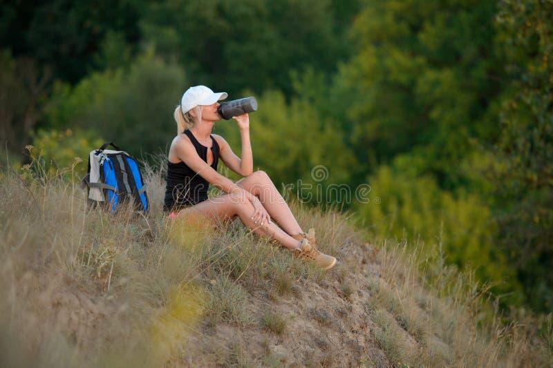 Het mooie drinkwater van het wandelaarmeisje Dorstige vrouwentoerist met bac stock afbeelding