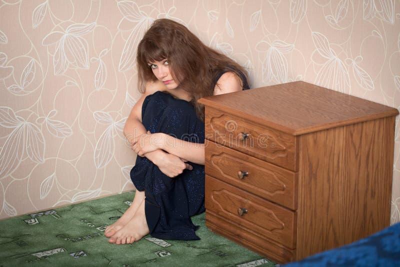 Het mooie droevige meisje in een kleding zit in een hoek stock foto's