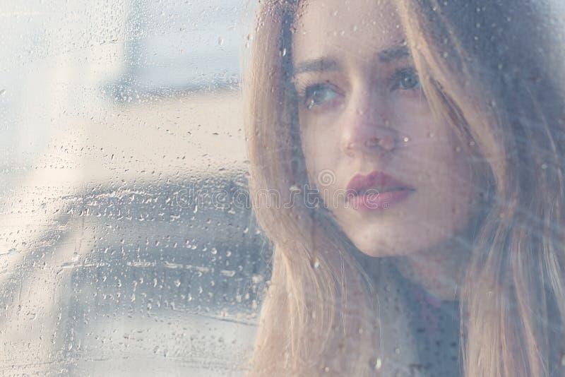 Het mooie droevige meisje met grote ogen in een laag is achter nat glas royalty-vrije stock fotografie