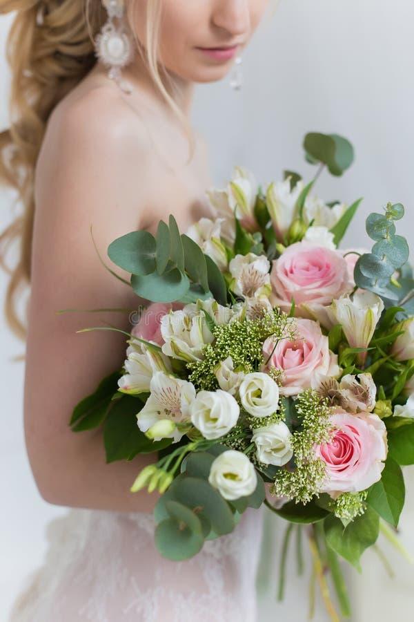 Het mooie elegante boeket van rozen en het groen in de zachte handen van het mooie bruidmeisje in een roze kleden de lucht stock foto