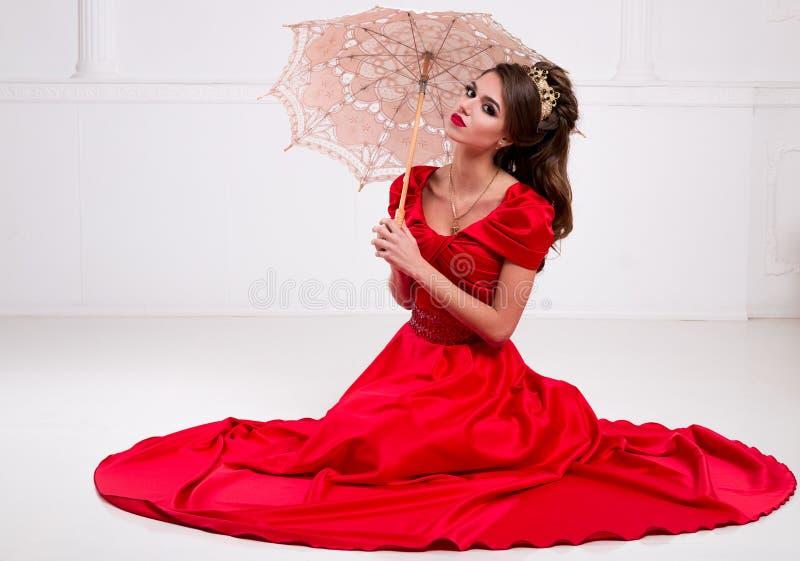 Het mooie elegante meisje in een lange rode kleding en schoenen zit op stock foto