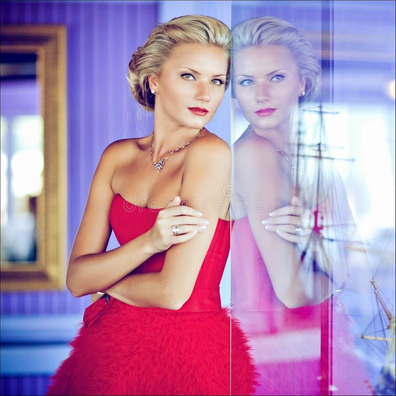 Het mooie elegante uitstekende blondemeisje in een rode kleding bevindt zich Ne royalty-vrije stock fotografie