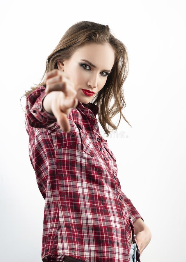 Het mooie emotionele meisjesmodel die met rode lippensamenstelling, een toevallig plaidoverhemd en jeans dragen richt haar vinger royalty-vrije stock afbeeldingen