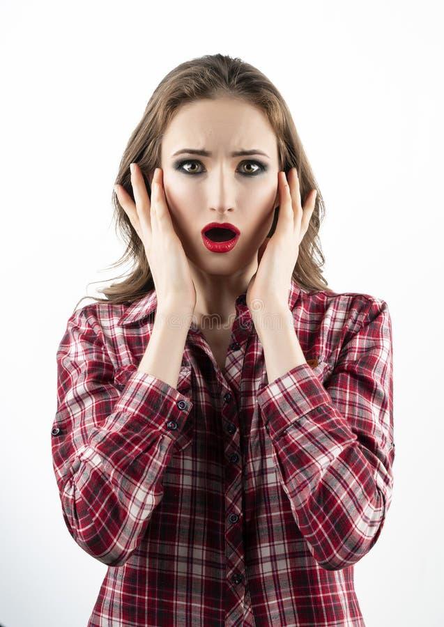 Het mooie emotionele meisjesmodel die met rode lippensamenstelling, een toevallig plaidoverhemd en jeans in verrassing dragen ope royalty-vrije stock afbeeldingen