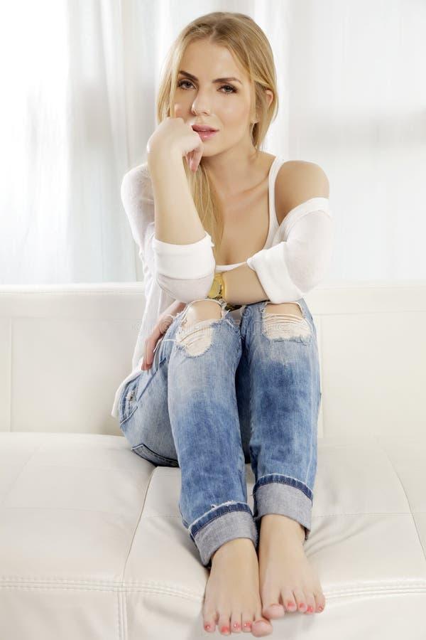 Het mooie en aantrekkelijke blondevrouw stellen in jeanskleding royalty-vrije stock foto