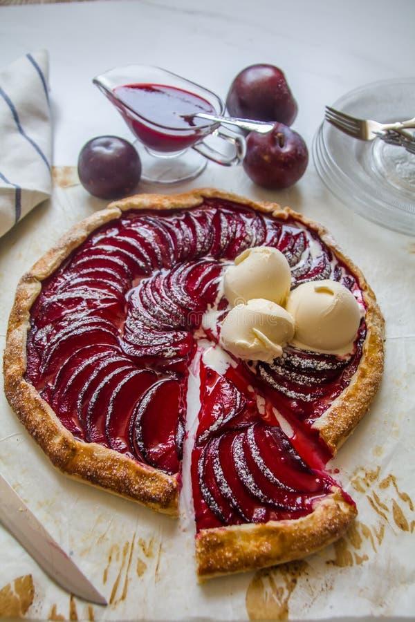 Het mooie en heerlijke huis maakte robijnrode rode pruimgalette na bakken gediend met pruimsaus en drie ballen van het vanilleroo stock afbeelding