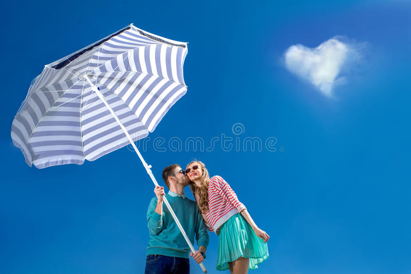 Het mooie en jonge paar kussen met strandparaplu op blauw s royalty-vrije stock foto's