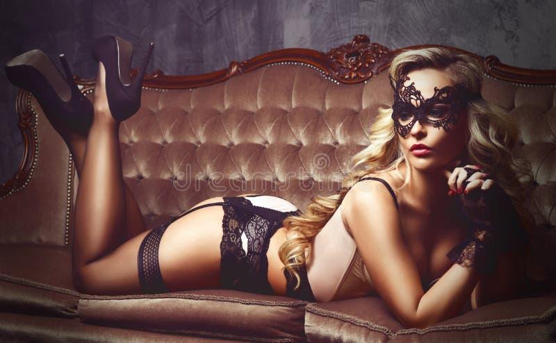 Het mooie en jonge vrouw stellen in sexy lingerie en Venetiaans m royalty-vrije stock afbeeldingen