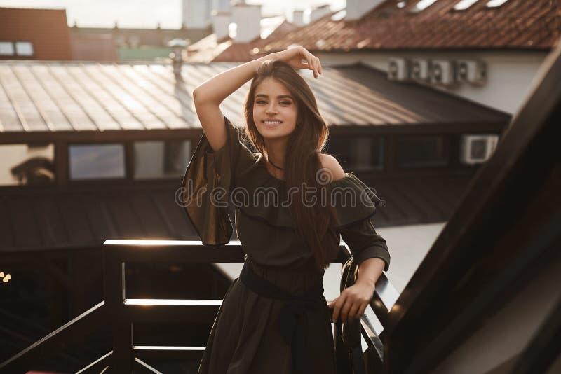 Het mooie en modieuze donkerbruine modelmeisje in modieuze kleding met naakte schouders glimlacht en in openlucht stellend bij stock foto