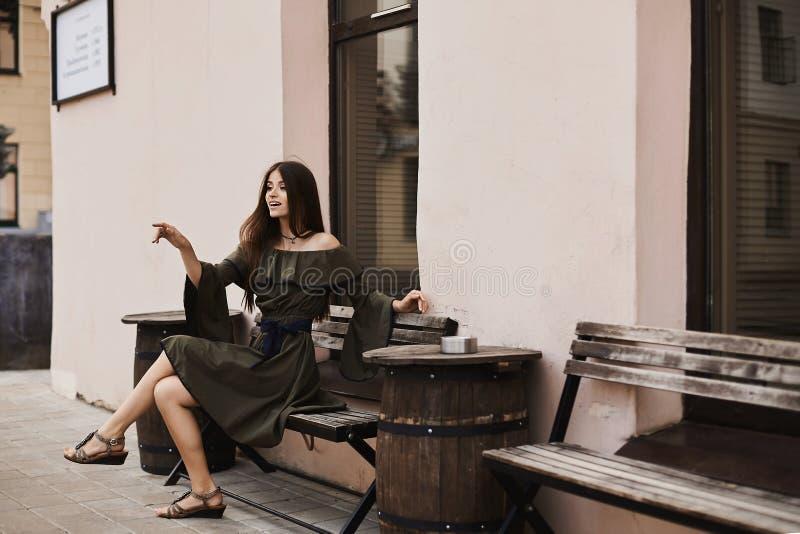 Het mooie en modieuze donkerbruine modelmeisje in modieuze kleding met naakte schouders zit op een bank en het stellen in openluc royalty-vrije stock foto