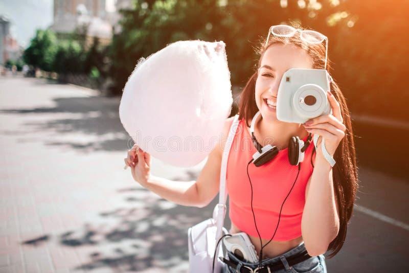 Het mooie en schitterende meisje bevindt zich en stellend als neemt zij beeld met haar witte camera Ook is het meisje royalty-vrije stock afbeeldingen