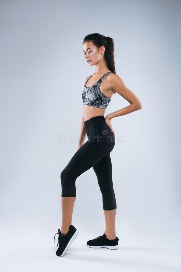 Het mooie en sexy sportvrouw stellen in studio over grijze achtergrond royalty-vrije stock fotografie