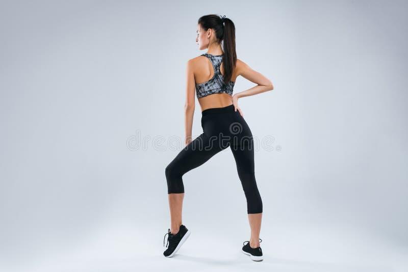 Het mooie en sexy sportvrouw stellen terug naar de camera in studio over grijze achtergrond stock afbeeldingen