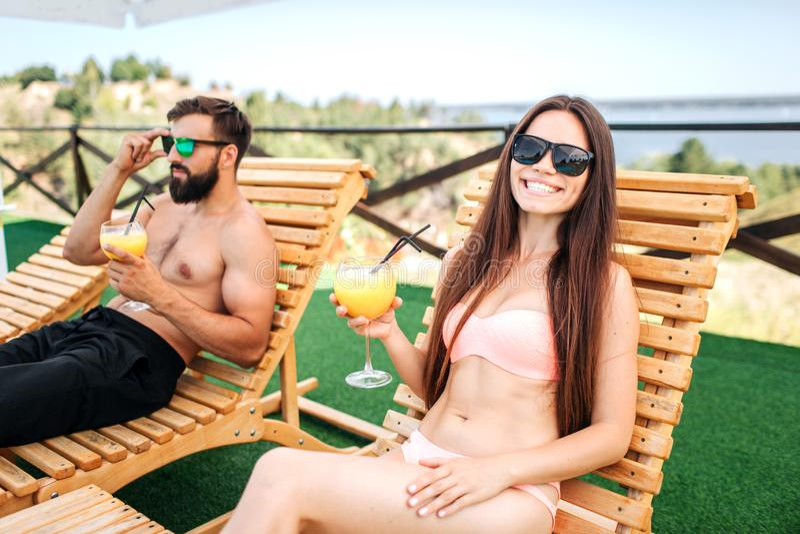 Het mooie en well-built paar ligt op sunbeds en heeft rust zij glazen cocktails in hebben Het meisje draagt zwemt stock foto