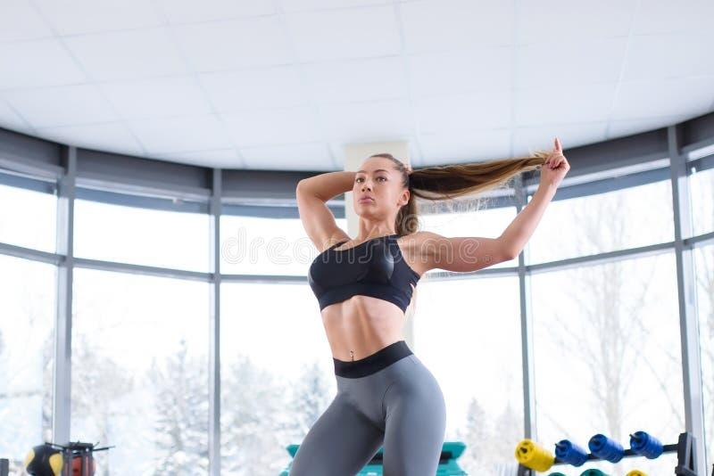 Het mooie fitness modelmeisje stellen in gymnastiek die sportkleren dragen Sportieve en gezonde vrouwenlevensstijl royalty-vrije stock afbeeldingen