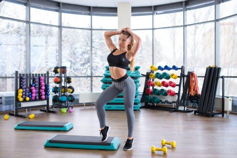 Het mooie fitness modelmeisje stellen in gymnastiek die sportkleren dragen Sportieve en gezonde vrouwenlevensstijl royalty-vrije stock foto