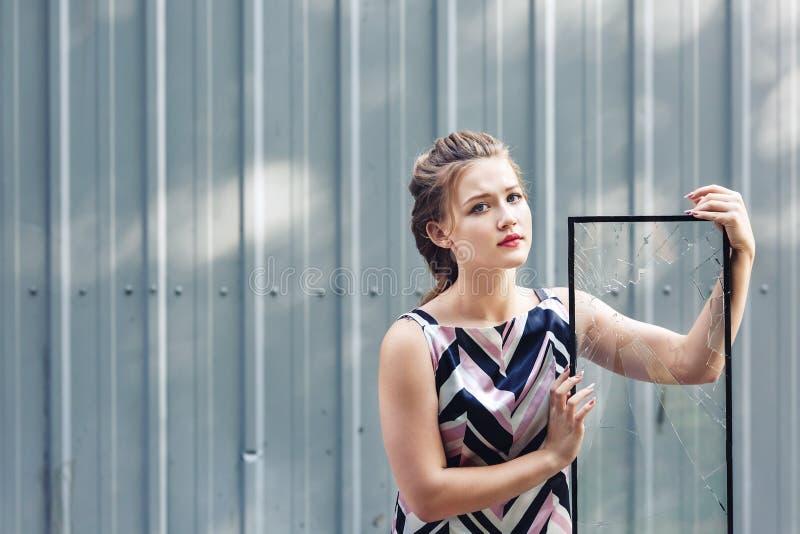 Het mooie gebroken glas van het tienermeisje holding in haar handen concept om uitdagingen in adolescentie te overwinnen stock afbeelding