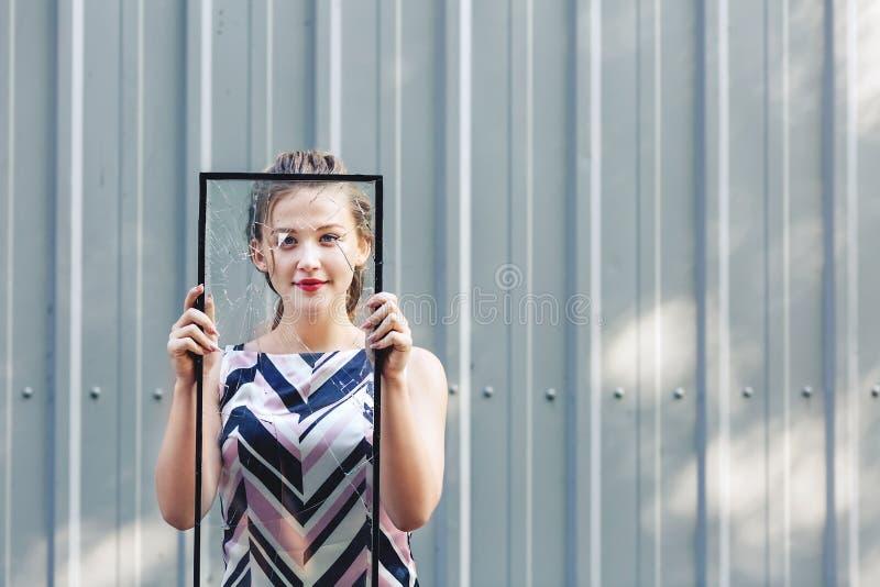 Het mooie gebroken glas van het tienermeisje holding in haar handen Conceptenfeminisme stock foto's