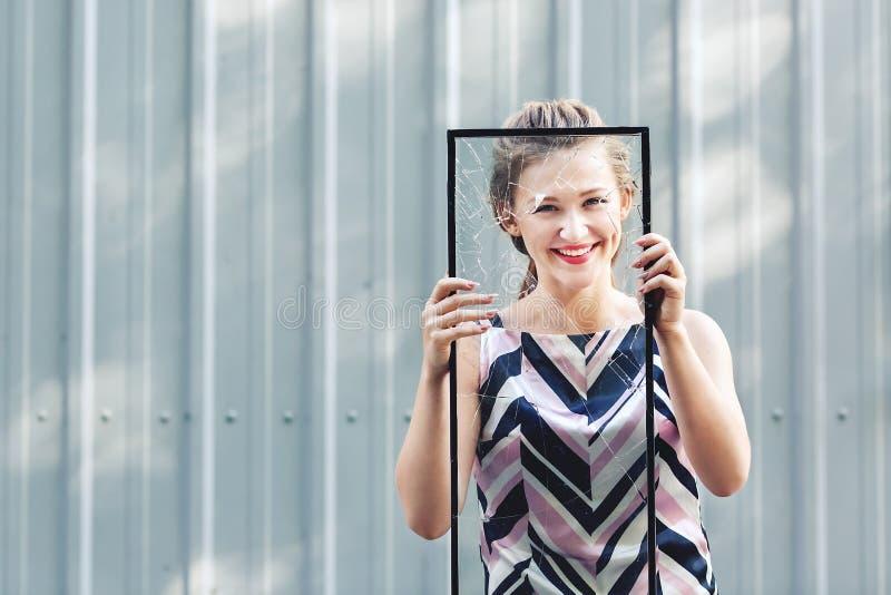 Het mooie gebroken glas van het tienermeisje holding in haar handen Conceptenfeminisme royalty-vrije stock fotografie