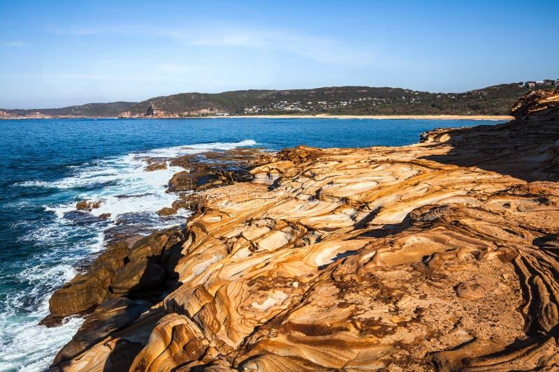 Het mooie gekleurde zandsteen schommelt dichtbij Stopverfstrand, het Nationale Park van Bouddi, Australië stock fotografie
