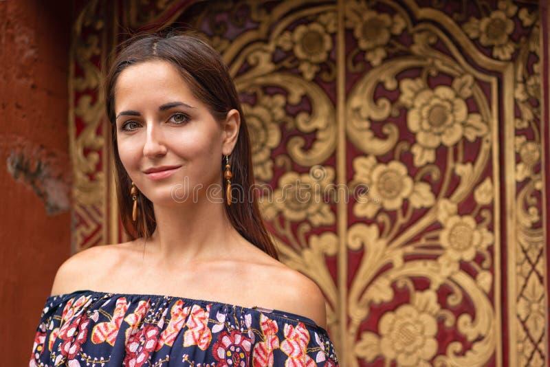 Het mooie gelooide jonge vrouw stellen op camera tegen een gevormde muur stock afbeeldingen