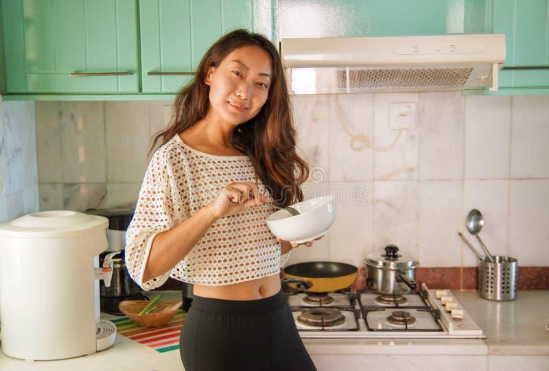 Het mooie gelukkige Aziatische vrouw koken bij keuken royalty-vrije stock foto