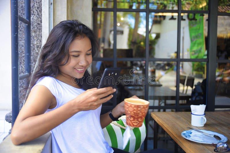 Het mooie gelukkige Aziatische vrouw ontspannen glimlachen genietend van ontbijt die mobiele telefoon met behulp van stock foto