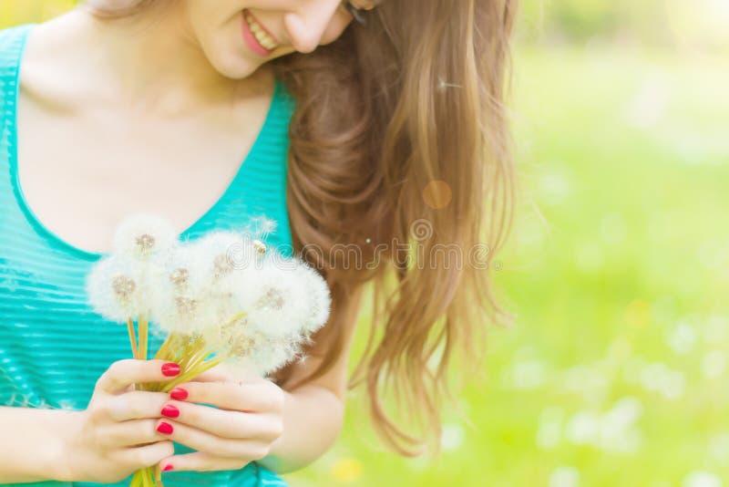 Het mooie gelukkige glimlachende meisje met lange paardebloemen in de handen van borrels en een t-shirt rust in het Park op een Z royalty-vrije stock afbeeldingen
