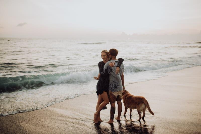 Het mooie gelukkige paar van lach jonge hipster met golden retriever op strand oceaan een zand Golven concepte van vrijheid en royalty-vrije stock afbeeldingen