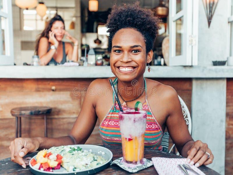Het mooie gemengde meisje van de ras vreedzame eilandbewoner in vegetarische koffie voor ontbijt met omslag en salade en verse me stock foto's