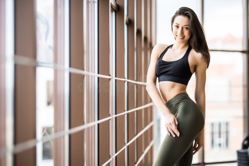 Het mooie geschiktheidsmeisje stellen die zich bij gymnastiek bevinden Portret van zekere sportieve vrouw met perfect lichaam Gez royalty-vrije stock fotografie