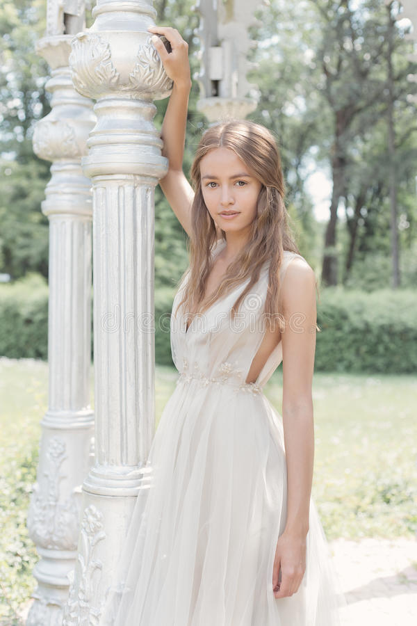 Het mooie gevoelige bruid sexy meisje in een lichte beige huwelijkskleding loopt in de tuin heldere zonnige warme dag royalty-vrije stock fotografie