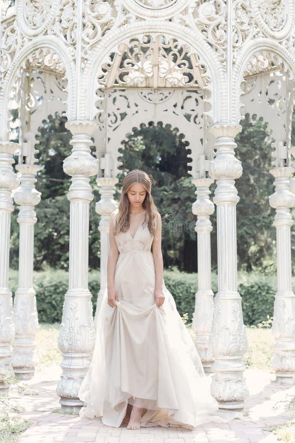 Het mooie gevoelige bruid sexy meisje in een lichte beige huwelijkskleding loopt in de tuin heldere zonnige warme dag stock fotografie