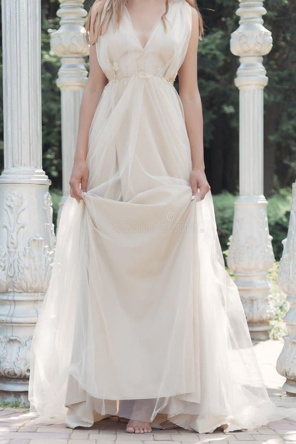 Het mooie gevoelige bruid sexy meisje in een lichte beige huwelijkskleding loopt in de tuin heldere zonnige warme dag stock afbeelding